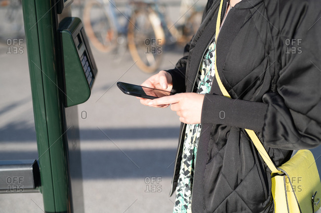 Close up of woman's hands using cellphone to verify payment for use of share bicycle