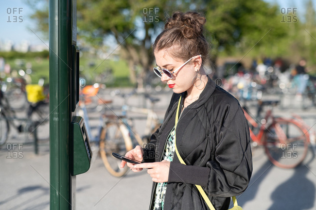 Side view of woman using cellphone to verify payment for use of share bicycle