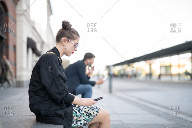 Young woman sitting on step checking smartphone for messages while waiting for friends