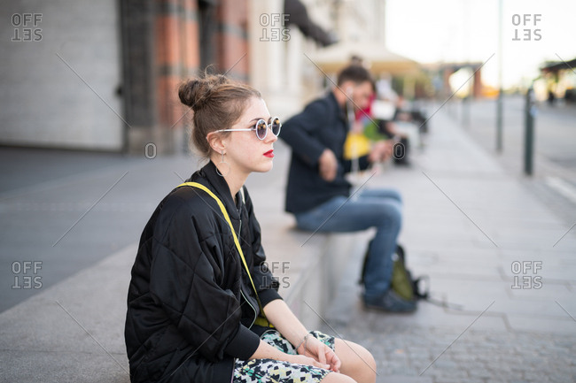 Young woman sitting on step waiting for friends in urban setting