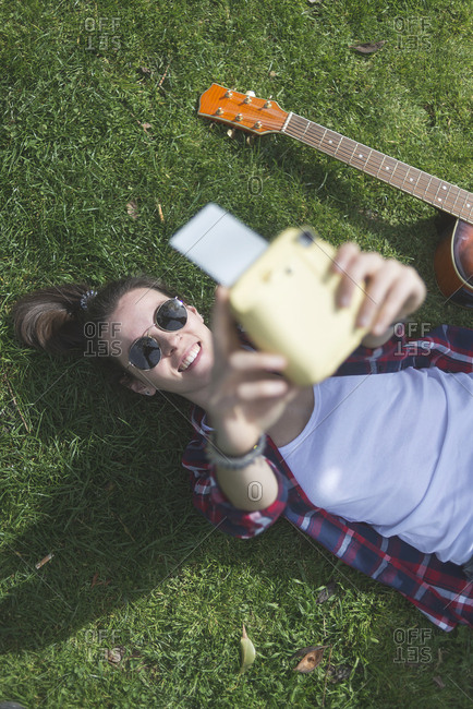 Teenager takes a selfie with an instant camera