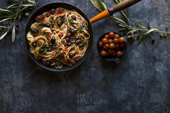 Spaghetti puttanesca olives in cast iron pan