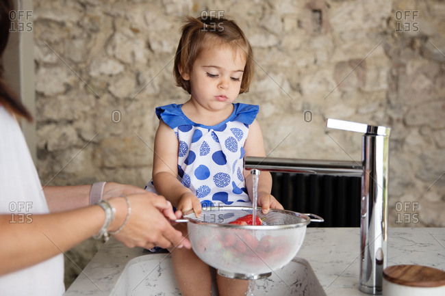 Little girl helping mom wash strawberries in the kitchen sink