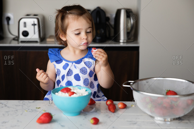 Little girl dipping strawberry into whip cream in the kitchen