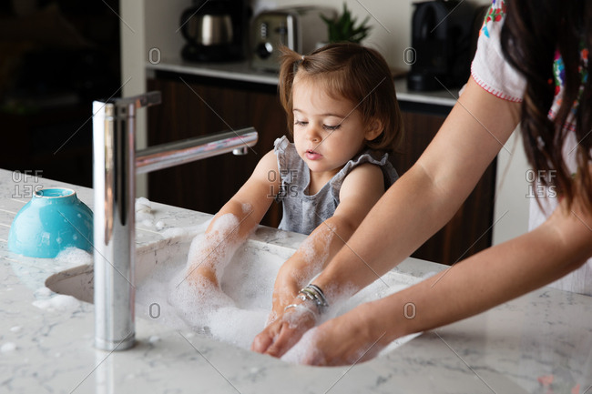 Little girl concentrating on washing dishes with mom