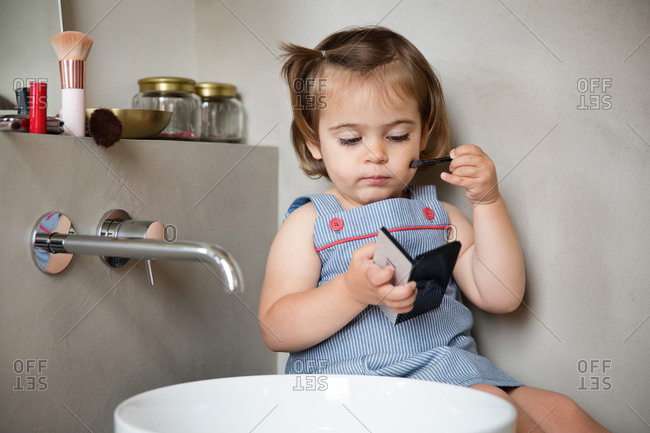 Curious toddler girl applying mom's makeup to cheeks alone in bathroom