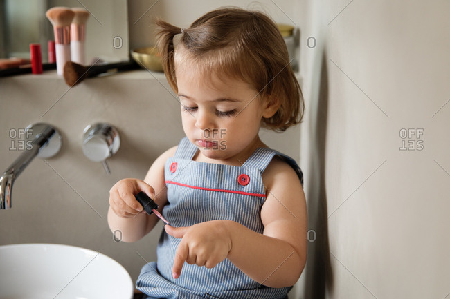 Young girl painting nails in bathroom alone