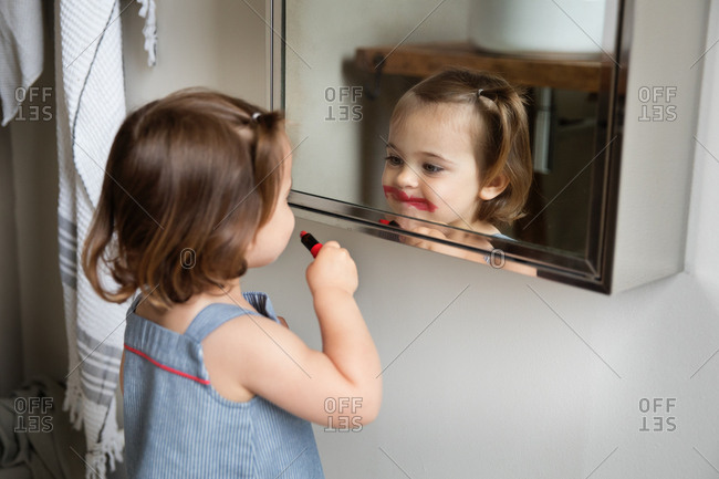 Small toddler girl admiring smeared lipstick in the bathroom mirror