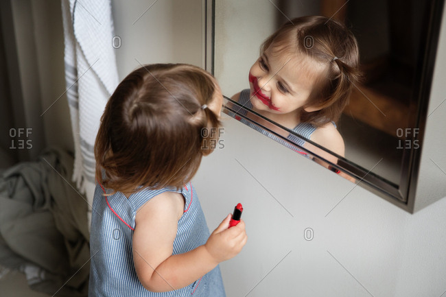 Cute preschooler with streak of lipstick on face smiling at herself in the mirror