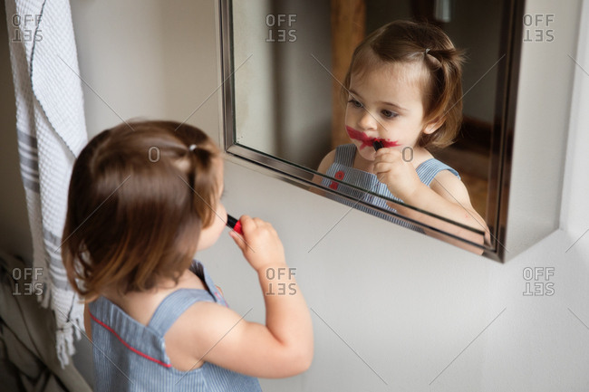 Playful little girl smearing mom's lipstick on face in the bathroom