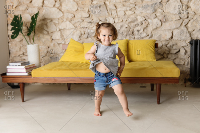 Happy toddler doing a silly dance in front of mid-century modern couch in living room