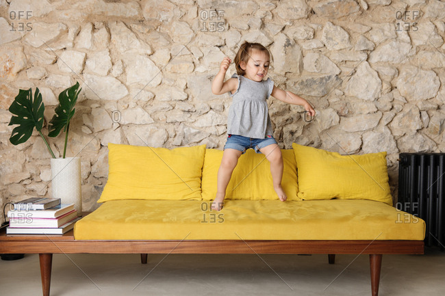 Little girl jumping on vibrant couch in retro decorated living room