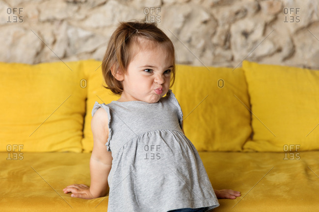 Funny toddler making silly faces on the couch