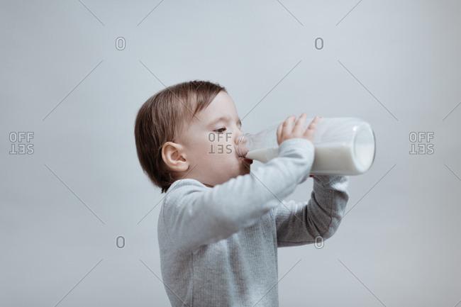 A little boy drinking milk against grey background