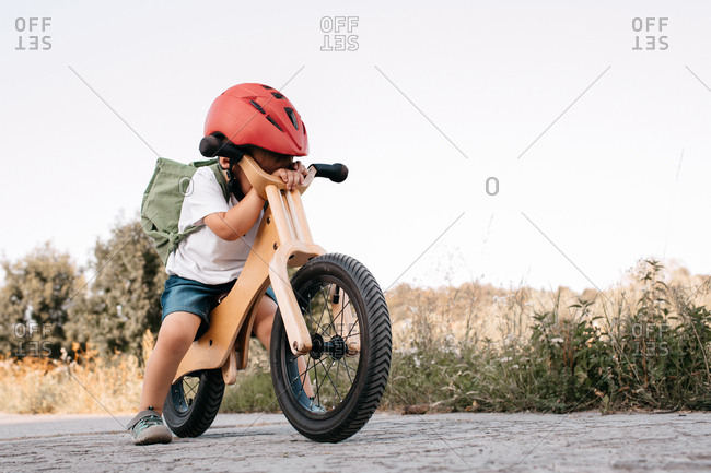 Portrait of a sad child sitting on a bicycle hiding his face