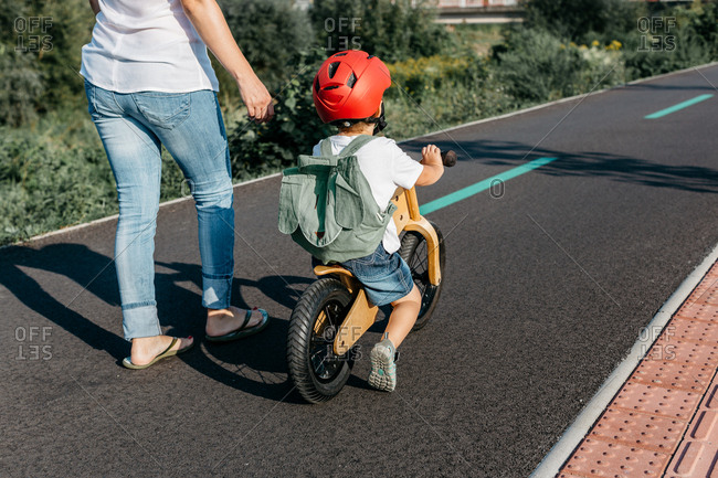 Rear view of a child riding his balance bike along a bicycle track