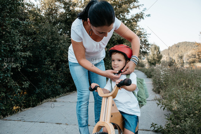 A mother helping her toddler boy to fasten a bicycle helmet