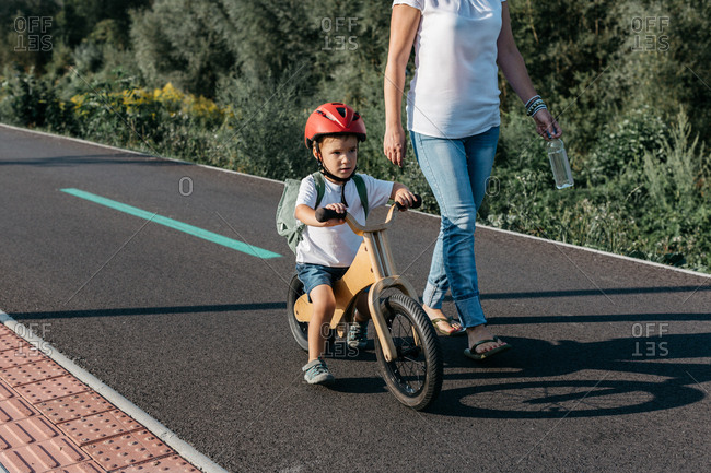 Front view of a child riding his balance bike along a bicycle track