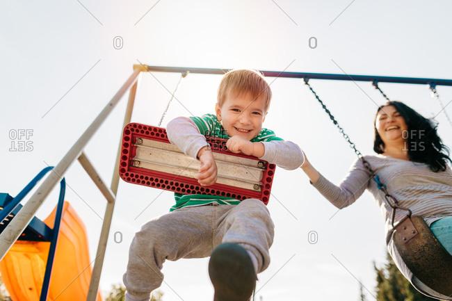 Cheerful boy having fun swinging with his mom