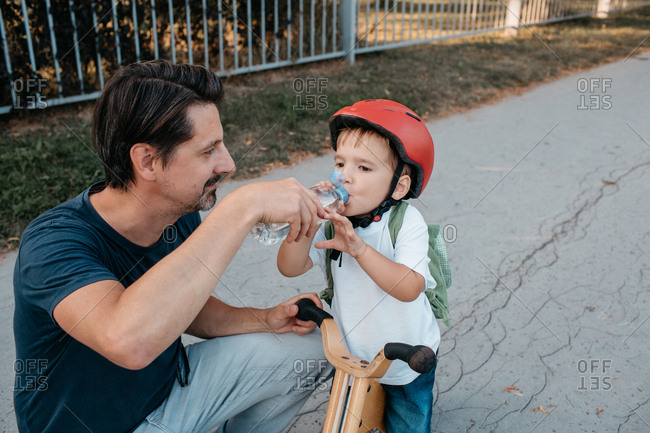 A father offering a bottle of water to his son on a balance bike