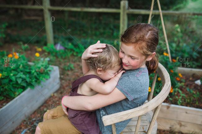 Young girl cuddling sleepy baby brother sitting in backyard