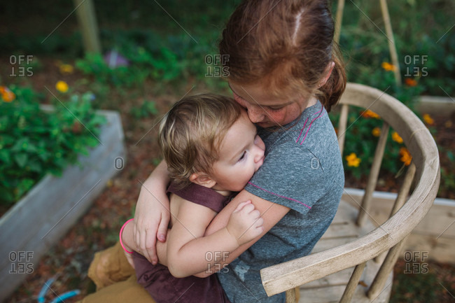 Young girl cuddling little brother while sitting in weathered chair in backyard