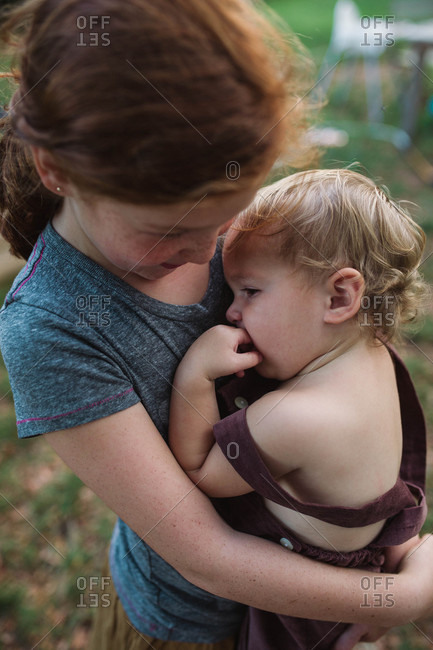Close up of young girl holding sleepy little brother in arms