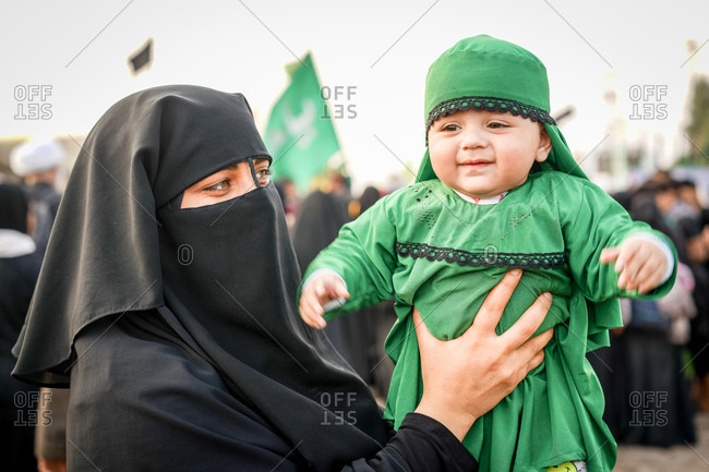 Karbala, Iraq - November 8, 2017: Portrait of a woman on the Arba'een Pilgrimage holding a baby boy