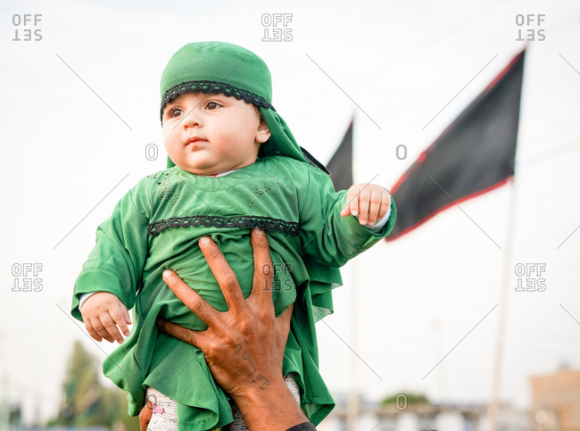 Karbala, Iraq - November 8, 2017: Person holding up baby boy in green outfit during the Arba'een Pilgrimage