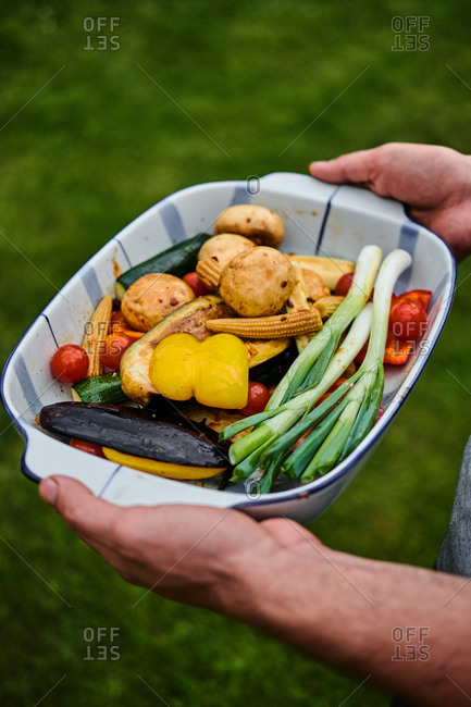 Close up of man's hands holding platter of uncooked seasonal vegetables ready to be grilled