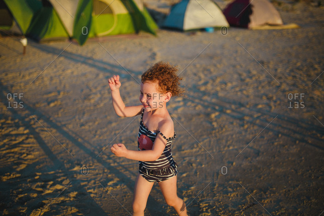 Little girl running through a campground on a sandy beach