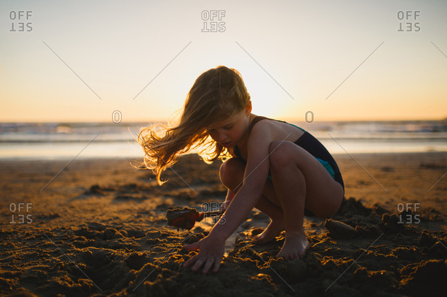 Girl playing in the sand on the beach at sunset