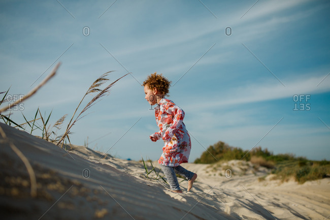 Young girl running across sand dune