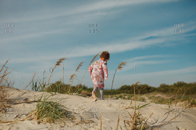 Girl walking across sand dune at the beach