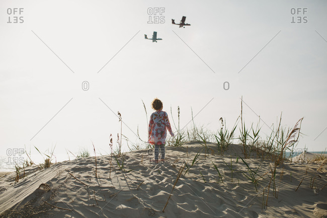 Young girl standing on sand dune watching airplanes in the sky