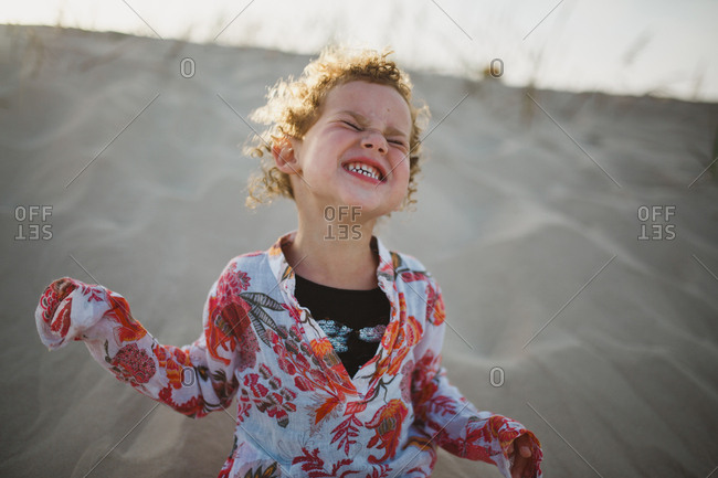 Joyful young girl running across dune