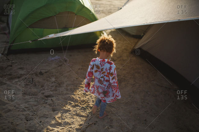 Girl playing on beach at sunset between tents at a campground