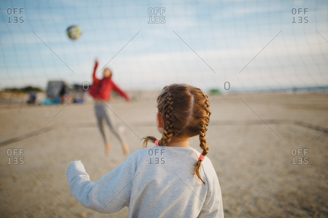Back view of a girl with braids playing volleyball