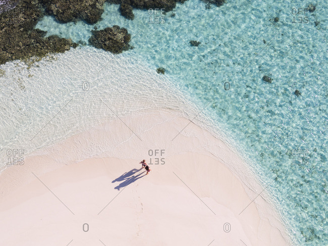 Aerial drone view of adult couple on a sandy beach, Maldives