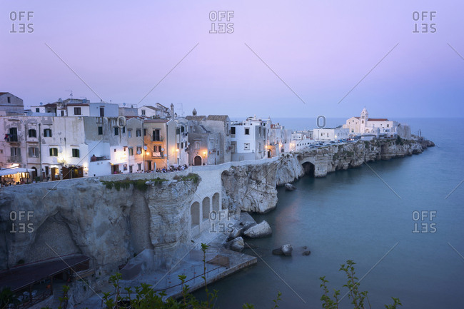 Apulia, Italy - September 18, 2012: Traditional houses on a cliff on the Mediterranean sea at sunset