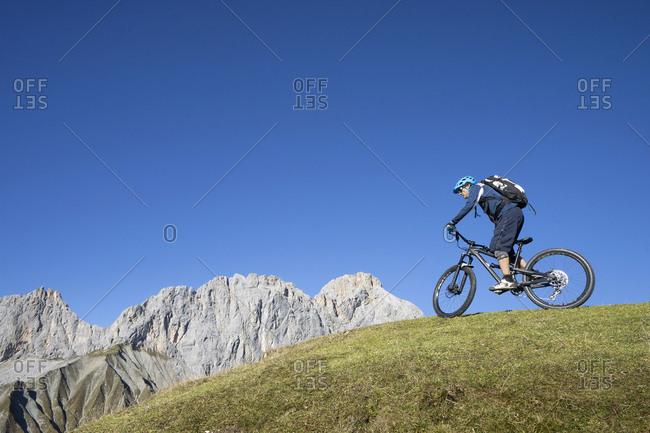 Mountain biker riding on uphill in alpine landscape, Tyrol, Austria