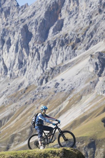 Mountain biker enjoying panoramic view on top of mountain, Tyrol, Austria