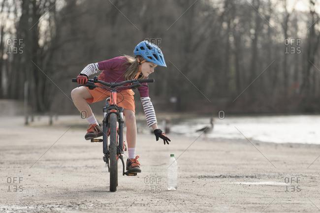 Female mountain biker picking up a bottle while training on mountain bike, Bavaria, Germany