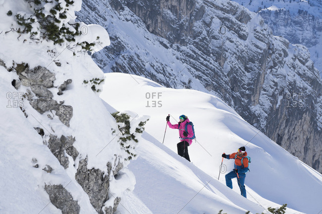 Couple climbing up the ski slope, Bavaria, Germany, Europe