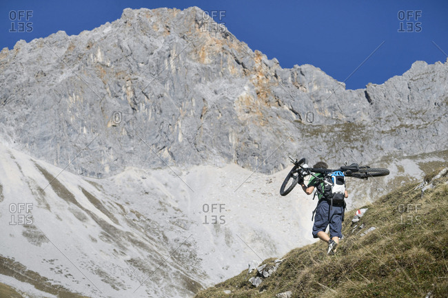 Mountain biker carrying bicycle on his shoulders, Tyrol, Austria