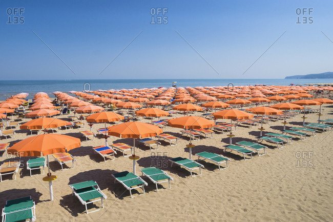 Umbrellas on sandy beach in Apulia, Italy