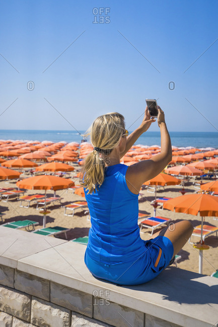 Woman taking selfie using mobile camera at sandy beach in Apulia, Italy