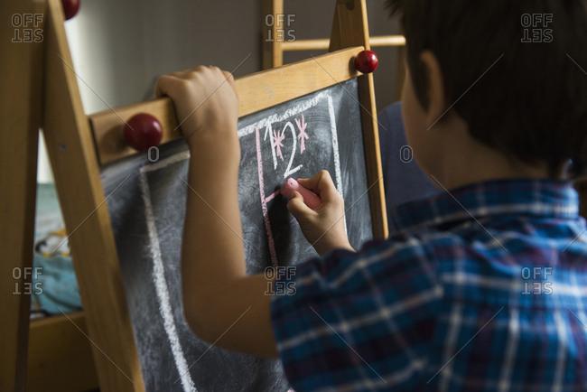 Close-up of a boy writing on a blackboard, Munich, Germany