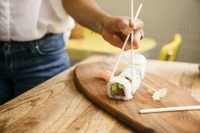 Closeup of woman's hand having sushi with chopsticks at wooden table