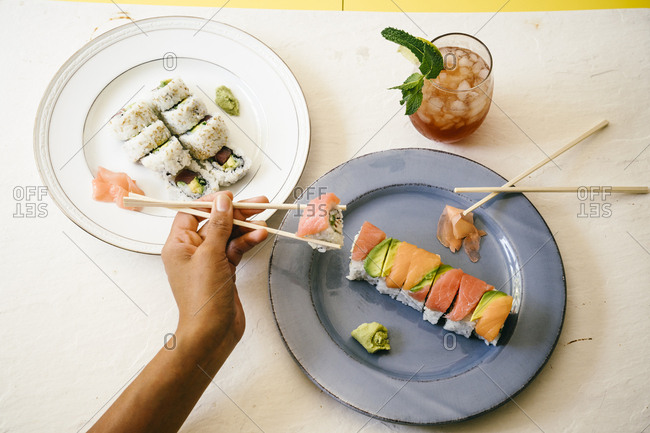 High angle view of hand holding sushi with chopsticks at table